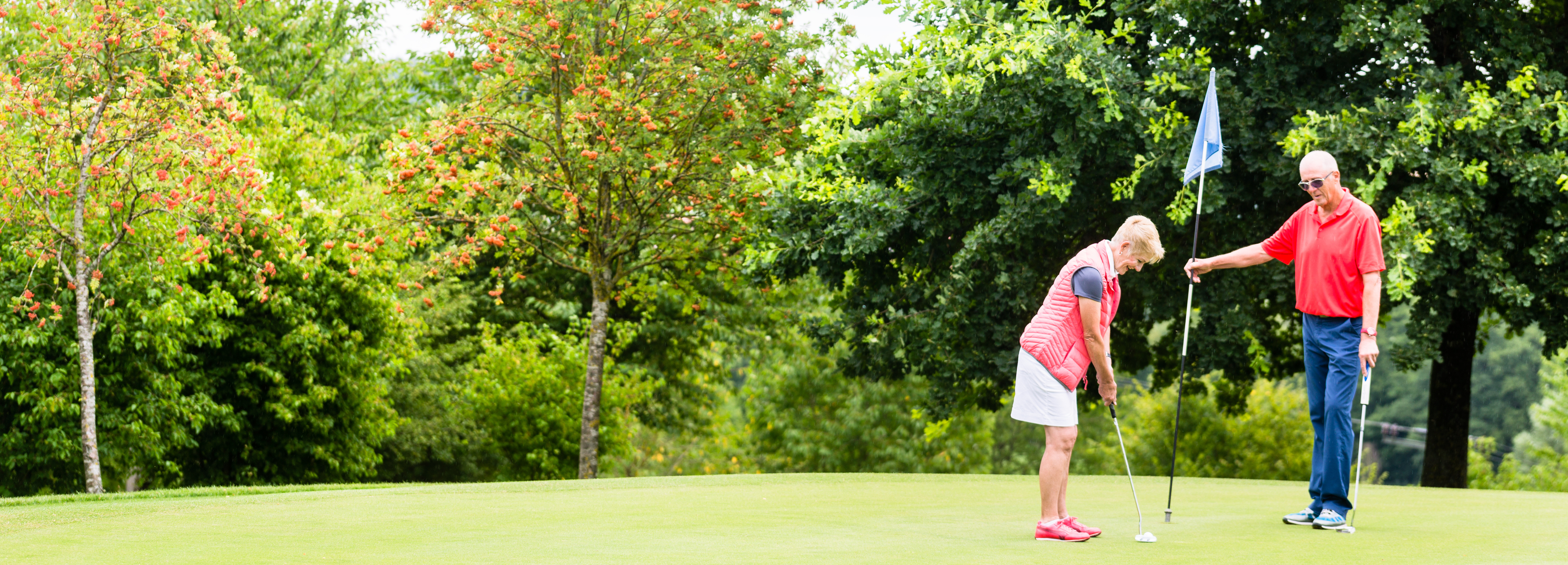 An image of a senior couple playing golf.