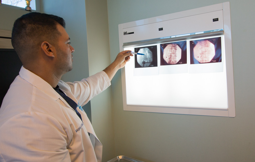 Dr. Waqaas Quraishi examining a patient's x-rays at the Orthopedic Spine Care of Long Island office.